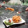 กุ้งชุบแป้งทอด วางบนผลไม้สดในตะกร้าเผือกทอด ราดด้วยครีมซอสของทางร้าน