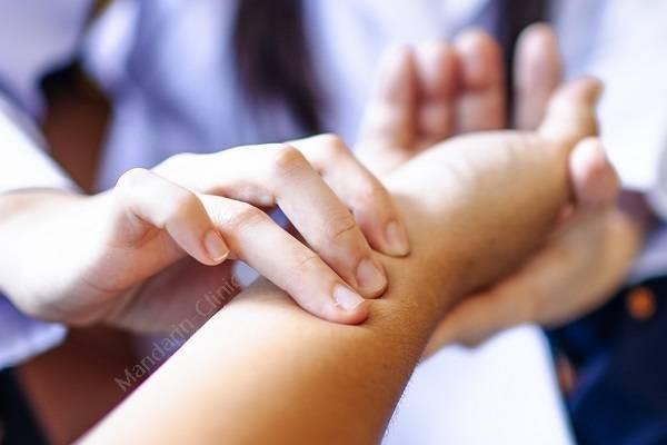 การฝังเข็มที่แมนดารินคลีนิกแพทย์ผู้เชี่ยวชาญจะตรวจสุขภาพโดยการจับชีพจรการเต้นของ
