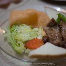 สเต็กหมูเสริฟมาพร้อมกับผัก ขนมปัง ข้าวเกรียบกุ้ง
