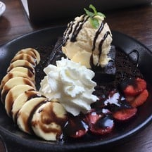 Hot Brownie With Slices Of Banana And Strawberry And Scoop Of Vanilla Ice Cream