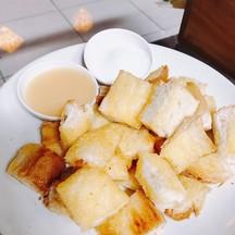 ขนมปังร้อนๆ เสิร์ฟพร้อมนมข้นหวานและน้ำตาล