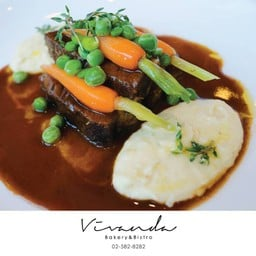 Braised beef cheeks in red wine sauce with mashed potato and young vegetables
