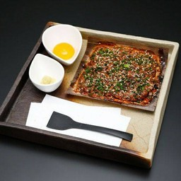 ไก่บดซึคุเนะบนแผ่นไม้ทานกับไข่ดิบและขิง