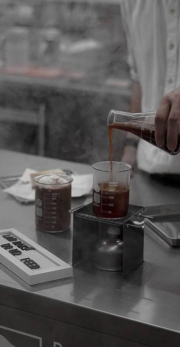 """เปลี่ยนโรงงานผลิตยาเก่าให้เป็นคาเฟ่ธีมห้องทดลองวิทยาศาสตร์ ร้าน """"Beaker and Bitter"""" คาเฟ่เปิดใหม่ย่านอารีย์ ที่ไม่ได้มีดีแค่กิมมิก แต่ยังสนุกเหมือนให้เราได้ย้อนวัยเด็กไปอยู่ในห้องทดลองที่ตึกวิทย์ มีราวแขวนเสื้อชุดกาวน์และแว่นให้ใส่เป็นพร็อพถ่ายรูป"""