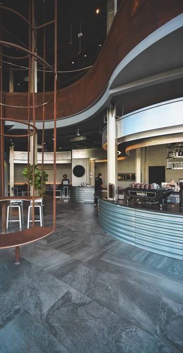 คาเฟ่ในอาคารรูปทรงแปลกตา แต่แอบซ่อนไปด้วยเมนูน่าสนใจมากมาย ภายในร้านโปร่งโล่งสบาย เหมาะกับการนั่งทำงานพร้อมจิบกาแฟแบบชิล ๆ