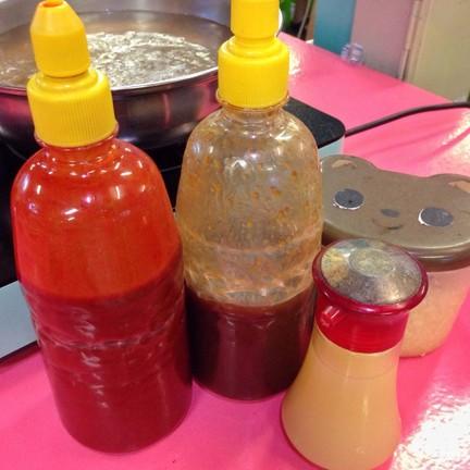 น้ำจิ้มเผ็ด > น้ำจิ้มหวาน > น้ำมะนาว > ด้านหลังคือพริกกระเทียมเติมไม่อั้น