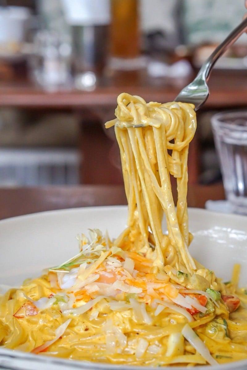 เส้น Linquine ปรุงกับซอสครีมผัดผงกะหรี่ใส่ปูด้วย ด้านบนมีไข่อ็อนเซน รสชาติมันๆ